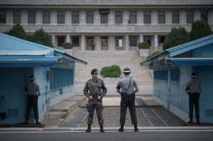 In a photo taken on August 2, 2017, South Korean soldiers stand guard before North Korea's Panmon Hall (rear C) and the military demarcation line separating North and South Korea, at Panmunjom, in the Joint Security Area (JSA) of the Demilitarized Zone (DMZ).. (Credit: ED JONES/AFP/Getty Images)