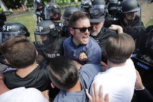 "White nationalist Richard Spencer, center, and his supporters clash with Virginia State Police in Emancipation Park after the ""Unite the Right"" rally was declared an unlawful gathering Aug. 12, 2017 in Charlottesville, Virginia. (Credit: Chip Somodevilla/Getty Images)"