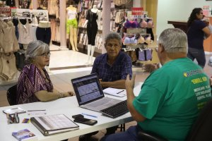 Isabel Diaz Tinoco, left, and Jose Luis Tinoco speak with Otto Hernandez, an insurance agent from Sunshine Life and Health Advisors, as they shop for insurance under the Affordable Care Act at a store setup in the Mall of Americas in Miami, Florida, on Nov. 1, 2017. (Credit: Joe Raedle / Getty Images)