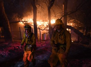 Firefighters move away from a burning house after discovering downed live power lines, as the Thomas wildfire continues to burn in Carpinteria, California, on Dec. 10, 2017. (Credit: Mark Ralston / AFP / Getty Images)