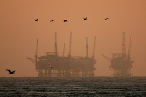 California brown pelicans fly near offshore oil rigs after sunset on July 21, 2009, near Santa Barbara. (Credit: David McNew/Getty Images)