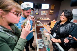 Tourists Laura Torgerson and Ryan Sheehan, visiting from Arizona, smell cannabis buds at the Green Pearl Organics dispensary in Desert Hot Springs on the first day of legal recreational marijuana sales in California, Jan. 1, 2018. (Credit: Robyn Beck / AFP / Getty Images)
