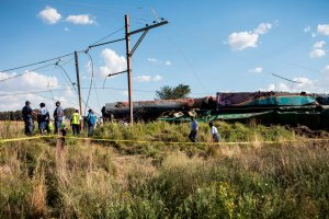 Members of the South African Police Service and Passenger Rail Agency South Africa look at a derailed train locomotive after an accident near Kroonstad in the Free State Province on Jan. 4, 2018. (Credit: Wikus de Wet/AFP/Getty Images)