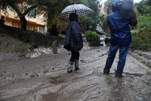 Journalists stand in ankle-deep mud after a rain-driven mudslide destroyed two cars and wrecked property in a Burbank neighborhood under mandatory evacuation on Jan. 9, 2018. (Credit: Robyn Beck / AFP / Getty Images)
