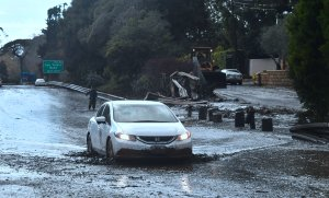A vehicle drives across a flooded US 101 freeway near the San Ysidro exit in Montecito on Jan. 9, 2018. (Credit: Frederic J. Brown/AFP/Getty Images)