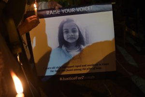 Pakistani civil society activists hold candles and placard with an image of Zainab, who was raped and murdered in the city of Kasur in Pakistan on Jan. 11, 2018 during a vigil in tribute to the child. (Credit: Aamir Qureshi / AFP / Getty Images)