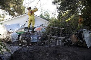 A Cal Fire firefighter looks through a car next to a Montecito home that was destroyed by a mudslide, Jan. 12, 2018. (Credit: Justin Sullivan / Getty Images)