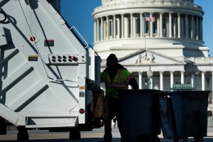 A trash collector removes garbage from Capitol Hill just as the government begins a shutdown on Jan. 20, 2018. (Credit: Brendan Smialowski / AFP / Getty Images)