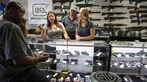 Store managers Jamie Taflinger, left, and Kendyll Murray show customer Cornell Hall, of Highland, Calif., different types of ammunition at the Get Loaded gun store in Grand Terrace in 2016. (Credit: Gina Ferazzi / Los Angeles Times)