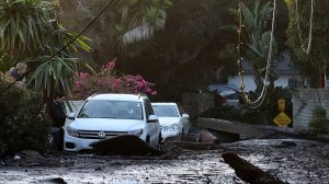 A resident looks into her car that sits in mud and debris from a mudslide on Jan. 11, 2018, in Montecito. (Credit: Justin Sullivan/Getty Images)