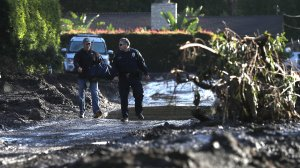 A police officer escorts a resident through a neighborhood that was destroyed by a mudslide on Jan. 12, 2018, in Montecito. (Credit: Justin Sullivan/Getty Images)