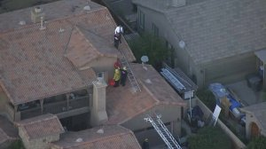 Authorities respond to a home on which a skydiver landed in Perris on Jan. 22, 2018. (Credit: KTLA)