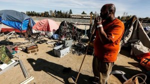 Arthur Johnson looks out toward his belongings on the ground that will need to be cleaned up and stored as Orange County officials started clearing homeless camps in that area of the Santa Ana riverbed on Jan. 22, 2018. (Credit: Maria Alejandra Cardona / Los Angeles Times)