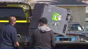 Crews retrieve an ATM from a dump truck in Lynwood on Feb. 25, 2018. (Credit: KTLA)