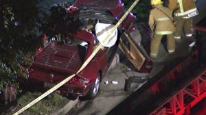 Firefighters work the scene near a Ferrari involved in a fatal crash in Pacific Palisades on Feb. 13, 2018. (Credit: KTLA)