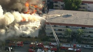 Firefighters battle a fire at an apartment building in Pico Rivera on Feb. 22, 2018. (Credit: KTLA)