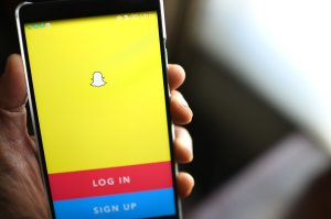 The Snapchat log-in page is displayed on a mobile phone. (Credit: ROBYN BECK/AFP/Getty Images)