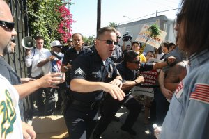 Los Angeles police officers try to clear the perimeter after angry medical marijuana advocates and protestors watched plainclothes federal Drug Enforcement Administration (DEA) agents tackle and arrest a protestor during a DEA raid of a Los Angeles medical marijuana dispensary, July 25, 2007. (Credit: Robyn Beck / AFP / Getty Images)