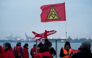 Members of the metalworkers' and electrical industry union (IG Metall) hold an Ig Metall flag and a placard displaying an Airbus plane during a warning strike near a ferry dock in Teufelbrueck, northern Germany on February 02, 2018. (Credit: DANIEL REINHARDT/AFP/Getty Images)