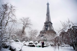 People walk through the snow covered Champ de Mars garden near the Eiffel tower on February 7, 2018 following heavy snowfall in Paris. (Credit: ALAIN JOCARD/AFP/Getty Images)