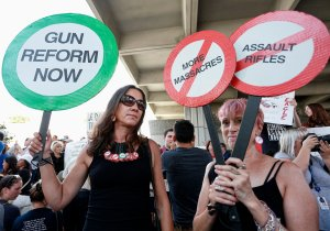 Protesters Alessandra Mondolfi (left) and Mercedes Kent (right) hold signs at a rally for gun control at the Broward County Federal Courthouse in Fort Lauderdale, on Feb. 17, 2018. (Credit: Rhona Wise/AFP/Getty Images)