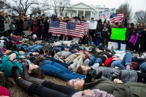 "Demonstrators lie on the ground a ""lie-in"" demonstration supporting gun control reform near the White House on Feb. 19, 2018. (Credit: Zach Gibson / Getty Images)"