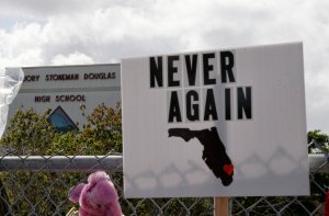 Memorials are seen on a fence surrounding Marjory Stoneman Douglas High School in Parkland, Florida, on Feb. 21, 2018. (Credit: RHONA WISE/AFP/Getty Images)