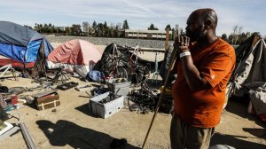 Arthur Johnson looks out toward his items that have to cleaned up and stored along the Santa Ana River. (Credit: Maria Alejandra Cardona / Los Angeles Times)