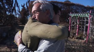 """Ansen """"Tony"""" Roberts and Zach Garcia embrace at the site of Roberts' burned-out home that was destroyed in the Thomas Fire. (Credit: KTLA)"""