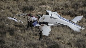 L.A. County sheriff's deputies inspect the site where a small aircraft crashed Sunday, killing four people in a remote area near Agua Dulce. (Credit: Robert Gauthier / Los Angeles Times)