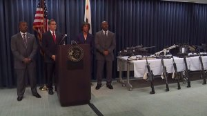 Attorney General Xavier Becerra, second from left, stands on Feb. 21, 2018, next to L.A. County District Attorney Jackie Lacey near a weapons cache seized at Steven Ponder's Temple City home. (Credit: KTLA)