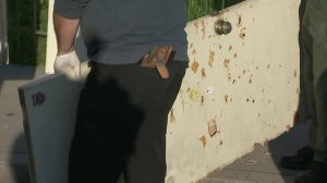 A door riddled with bullet holes is removed from the scene where one police officer was fatally shot and another wounded in Pomona, March 11, 2018. (Credit: KTLA)