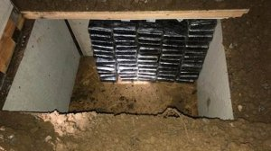 Stacks of cocaine are seen inside an underground bunker that was discovered in the backyard of an Inland Empire home where investigators uncovered about $8.4 million in cocaine. Authorities announced the seizure and arrests of two men in connection with it on March 23, 2018. (Credit: Orange County Sheriff's Department)