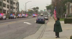 A woman holds up an American flag during a procession for a fallen officer in Pomona on March 10, 2018. (Credit: KTLA)