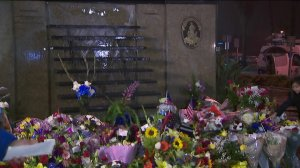 Hundreds of flowers adorn the wall outside the Pomona police headquarters where Officer Gregg Casillas' name will be inscribed among other fallen officers, March 10, 2018. (Credit: KTLA)