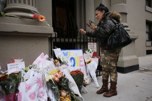 Angel Colone prays in front of the building where two children were stabbed to death allegedly by their nanny in a family's Upper West Side apartment on Oct. 26, 2012, in New York City. (Credit: Spencer Platt / Getty Images)