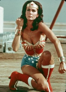 American actor Lynda Carter kneels on the ground and bears her forearm in a still from the television series Wonder Woman. (Credit: Warner Brothers/Getty Images)