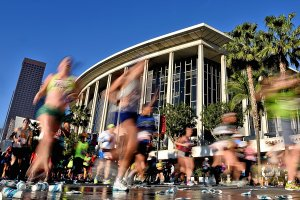 Runners stream past the Dorothy Chandler Pavilion and the Los Angeles Music Center during the 2016 Skechers Performance Los Angeles Marathon on Feb. 14, 2016. (Credit: Jonathan Moore / Getty Images)