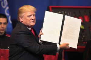 President Donald Trump signs an executive order to try to bring jobs back to American workers and revamp the H-1B visa guest worker program during a visit to the headquarters of tool manufacturer Snap-On on April 18, 2017 in Kenosha, Wisconsin. (Credit: Scott Olson/Getty Images)