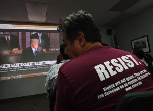 DACA recipients and their supporters watch President Donald Trump during a State of the Union party at the Coalition for Humane Immigrant Rights and the California Dream Network offices in Los Angeles on Jan. 30, 2018. (Credit: MARK RALSTON/AFP/Getty Images)