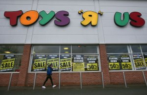 "A customer walks outside a Toys ""R"" Us store with ""closing down sale"" signs in the windows in south London on Feb. 9, 2018. (Credit: DANIEL LEAL-OLIVAS/AFP/Getty Images)"