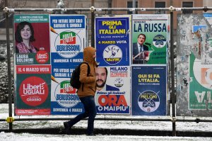 A pedestrian walks in front of election posters in Milan on March 1, 2018. (Credit: MIGUEL MEDINA/AFP/Getty Images)