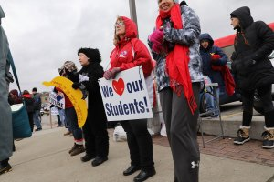 West Virginia teachers, students and supporters hold signs on a Morgantown street as they continue their strike on March 2, 2018, in Morgantown, West Virginia. (Credit: Spencer Platt/Getty Images)