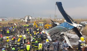 Nepali rescue workers gather around the debris of an airplane that crashed near the international airport in Kathmandu on March 12, 2018. (Credit: PRAKASH MATHEMA/AFP/Getty Images)