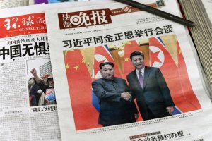 The front pages of Chinese evening newspapers, showing images of China's President Xi Jinping with North Korean leader Kim Jong Un, are displayed at a newspaper stand in Beijing on March 28, 2018. (Credit: FRED DUFOUR/AFP/Getty Images)
