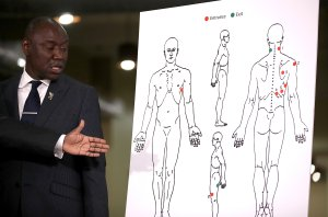 Attorney Ben Crump looks at a diagram showing gunshot wounds to Stephon Clark during a news conference in Sacramento on March 30, 2018. (Credit: Justin Sullivan / Getty Images)