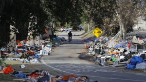 A cyclist passes trash from the Santa Ana River homeless camp in Anaheim in February after it was cleared and more than 700 people relocated. (Credit: Allen J. Schaben / Los Angeles Times)
