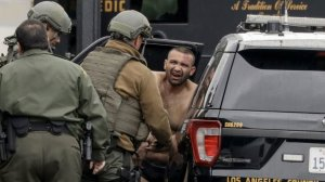 L.A. County sheriff's deputies escort Isaias De Jesus Valencia, suspected of fatally shooting a Pomona police officer, to a waiting car on Saturday. (Credit: Irfan Khan / Los Angeles Times)