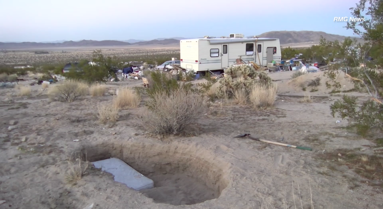 A small mattress is seen in a large, shallow hole on a property where two parents were arrested on suspicion of willful cruelty to a child on March 1, 2018. (Credit: RMG News)