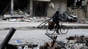 A person rides a bicycle through an area of destroyed homes local residents were searching through for their belongings in the Al-Asqalani neighborhood in Irbin town, Eastern Ghouta in Syria on Feb. 28, 2018. The neighborhood was bombed on Feb. 22, 2018, when civilians were left seeking refuge in basements. (Credit: Syrian American Medical Society via CNN)